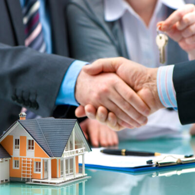 Estate agent shaking hands with customer after contract signature