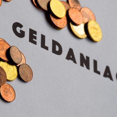 """verschiedene abgegriffene Geldmünzen mit Schriftzug """"Geldanlage"""""""
