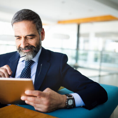 Elegant business multitasking multimedia man using devices at office