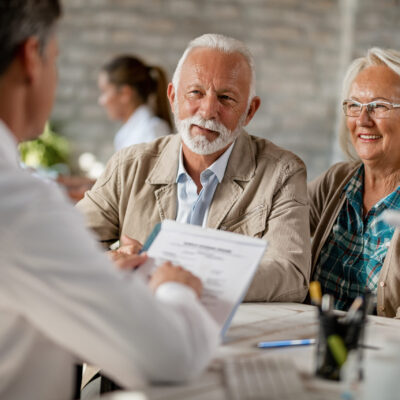 Happy mature couple informing themselves about health insurance while talking to a doctor at clinic.