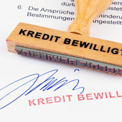 Ein Stempel aus Holz liegt auf einem Dokument. Aufschrift Kredit bewilligt